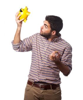 L'homme en chemise à carreaux regardant dans la tirelire