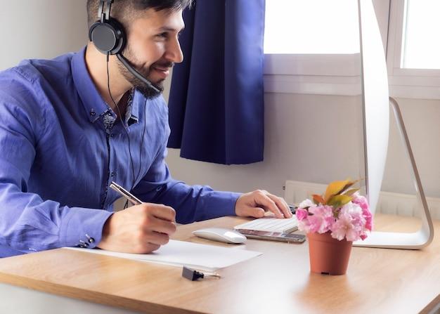 Homme en chemise et casque professionnel travaillant à domicile télétravail.