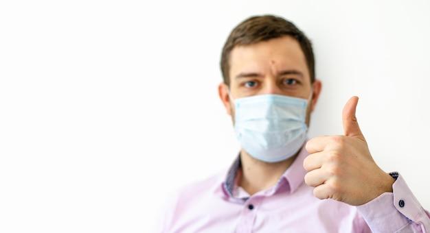 Un homme en chemise dans un masque de protection montrant les pouces vers le haut