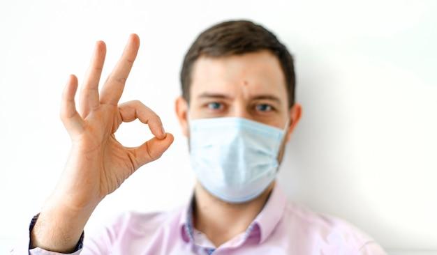 Un homme en chemise dans un masque de protection montre un signe correct