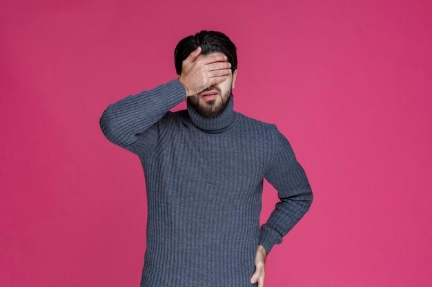 Homme en chemise grise tenant les mains dans sa taille comme s'il avait mal au dos.