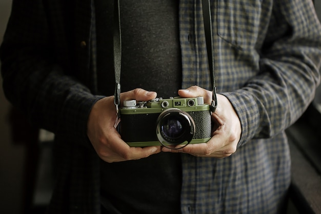 Homme en chemise homme mains détient caméra vert film rétro horizontal