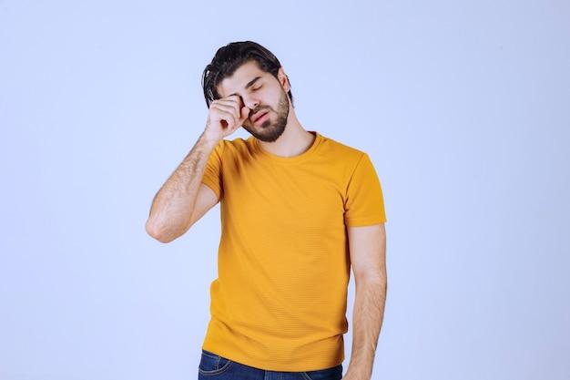 L'homme en chemise jaune a l'air endormi