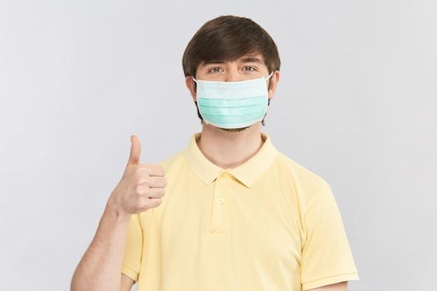 Homme en chemise jaune et masque stérile de protection montrant le geste du pouce vers le haut, bon signe de porter des masques de sécurité pendant le coronavirus