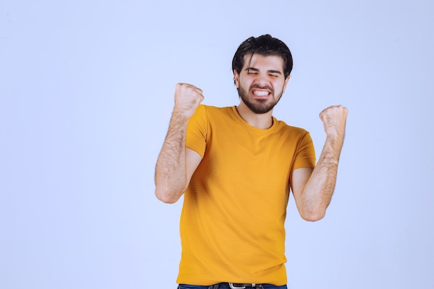 Homme en chemise jaune montrant son poing et son pouvoir.