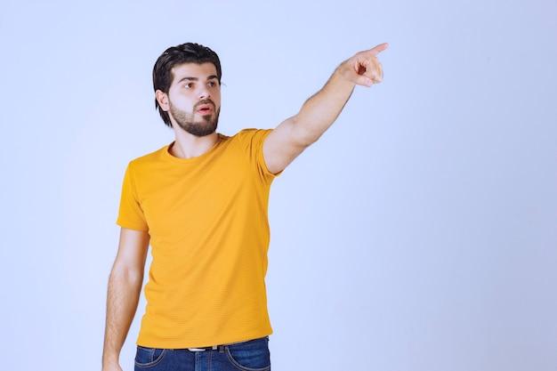 Homme en chemise jaune pointant vers quelqu'un à venir.