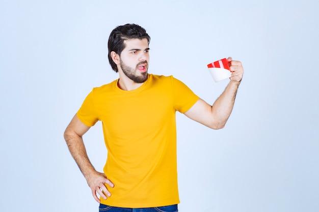 Homme en chemise jaune tenant une tasse rouge et pensant.