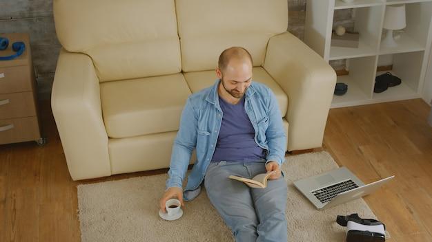 Homme en chemise en jean riant en lisant un livre et buvant du café sur le sol