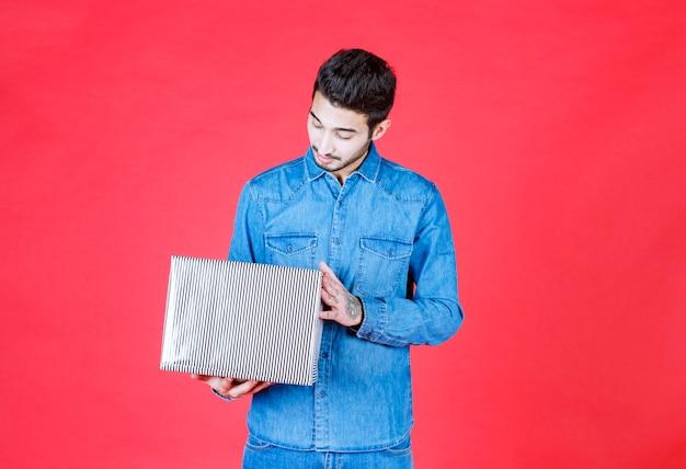 Homme en chemise en jean tenant une boîte-cadeau en argent et semble confus et inattendu.