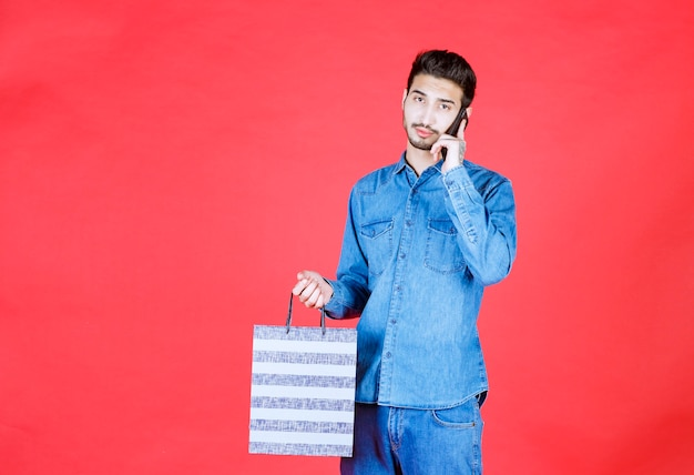 Homme en chemise en jean tenant une boîte à rayures et parler au téléphone.