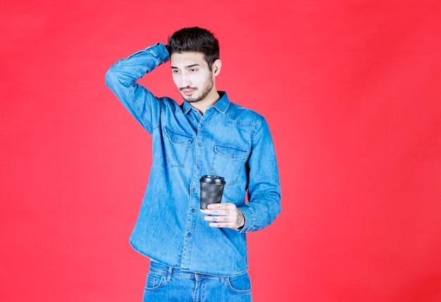 Homme en chemise en jean tenant une tasse de boisson jetable noire et a l'air pensif.