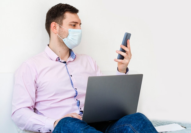 Un homme en chemise et jean travaille sur l'ordinateur portable et reste au téléphone