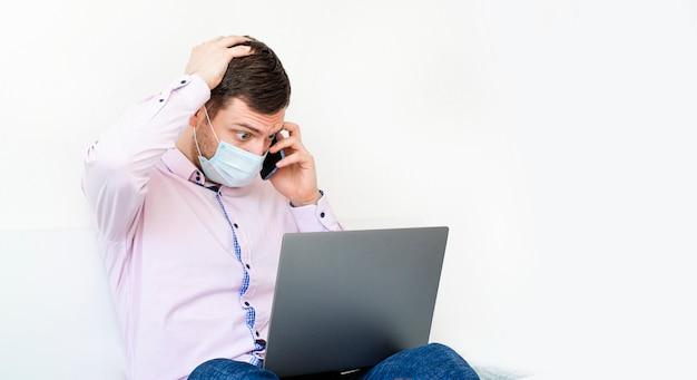 Un homme en chemise et jeans travaille sur l'ordinateur portable et parle au téléphone