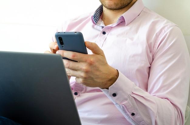 Un homme en chemise et jeans travaille sur ordinateur portable et téléphone