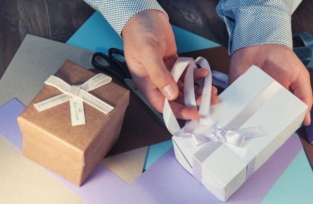 Un homme en chemise légère prépare une boîte-cadeau pour les vacances. tonifiant.