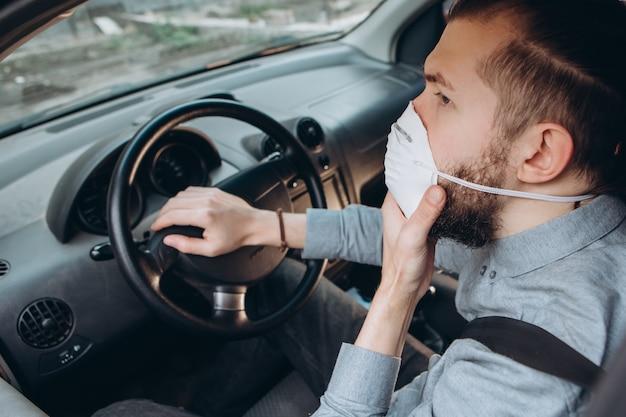 Homme en chemise et masque médical est assis au volant de la voiture.
