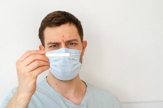 Un homme en chemise avec un masque mesure la température