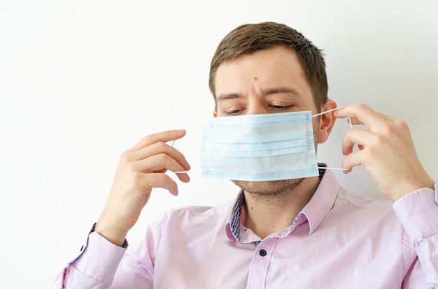 Un homme en chemise met un masque