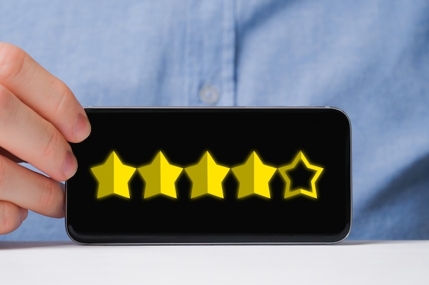 Un homme en chemise montre abstraitement une note de quatre étoiles sur cinq dans un smartphone. bonne note