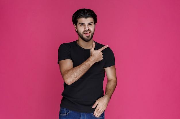 Homme en chemise noire avec barbe montrant quelque chose d'une manière confuse ou montrant la direction