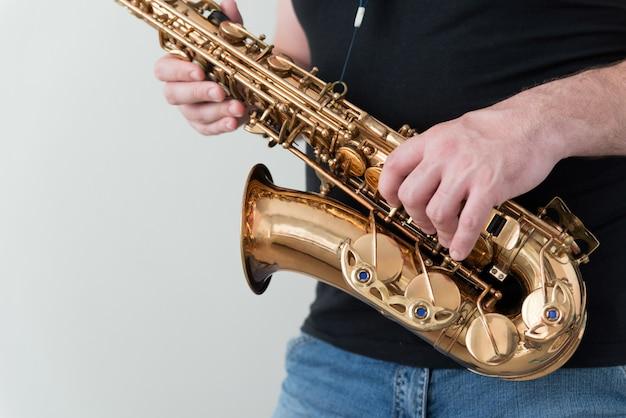 L'homme en chemise noire détient le saxophone
