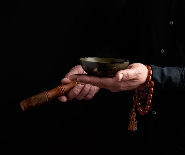 Un homme en chemise noire fait tourner un bâton en bois autour d'un bol tibétain en cuivre. rituel de méditation