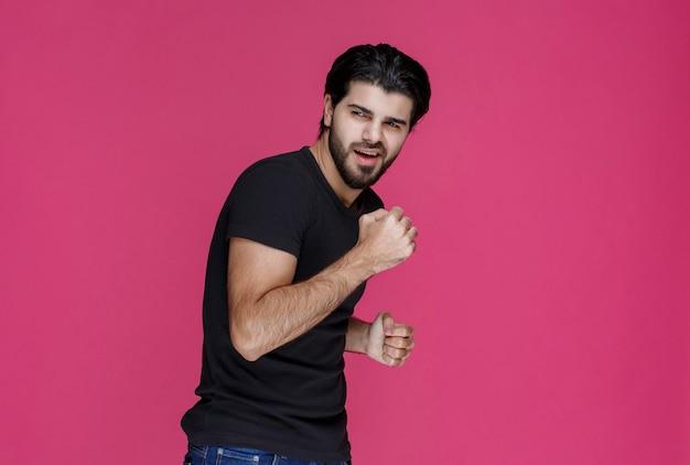 Homme en chemise noire montrant ses muscles du poing et des bras.