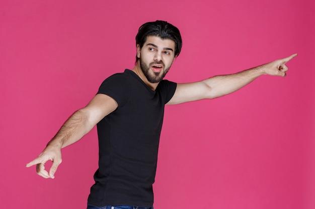 Homme en chemise noire présentant quelqu'un et le pointant
