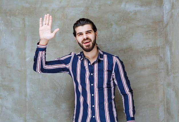 Homme en chemise rayée présentant quelqu'un avec passion.