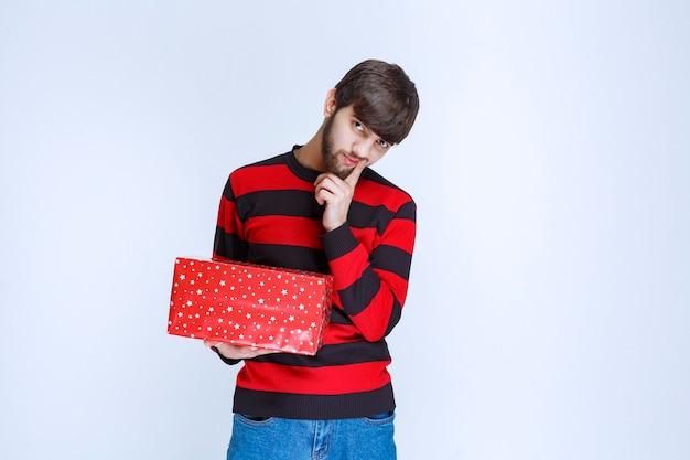 L'homme en chemise rayée rouge avec une boîte-cadeau rouge a l'air confus et réfléchi.