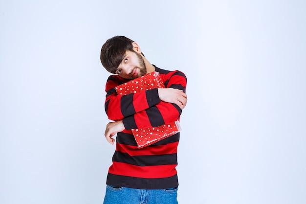 L'homme en chemise rayée rouge avec une boîte-cadeau rouge a l'air somnolent et épuisé.