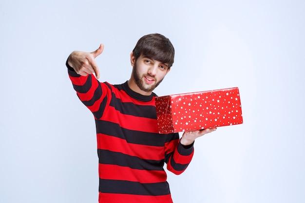 Homme en chemise rayée rouge avec une boîte-cadeau rouge et appelant quelqu'un pour le présenter.
