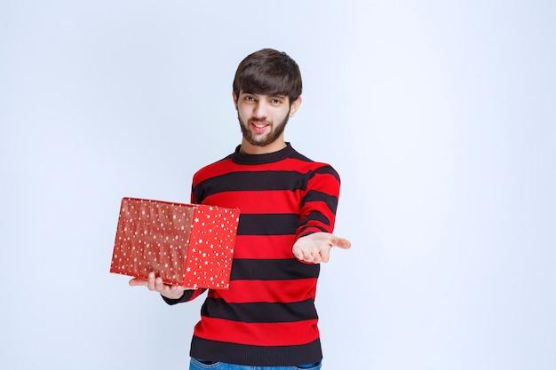 Homme en chemise rayée rouge avec une boîte cadeau rouge et l'offrant