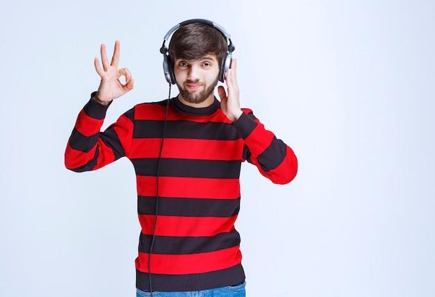 Homme en chemise rayée rouge écoutant des écouteurs et montrant un signe de plaisir.