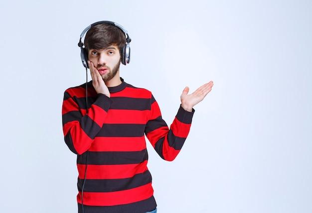 L'homme en chemise rayée rouge écoute des écouteurs et a l'air confus et réfléchi.