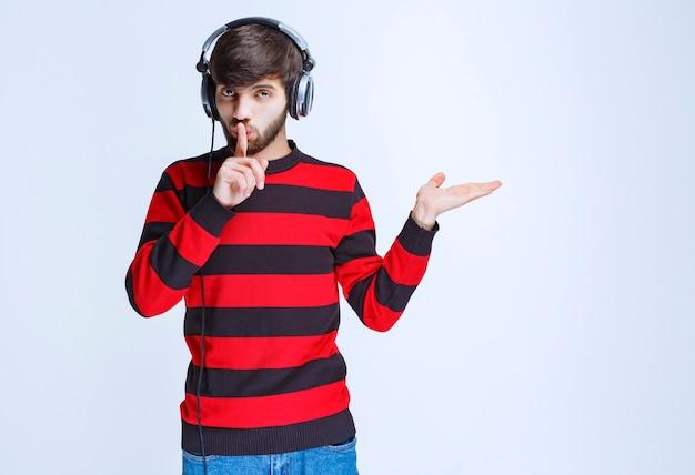 Homme en chemise rayée rouge portant des écouteurs et demandant le silence.