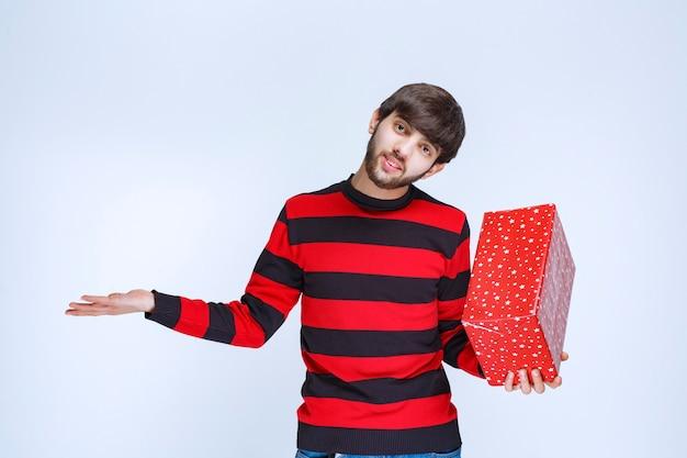 Homme en chemise rayée rouge tenant une boîte-cadeau rouge et a l'air confus et réfléchi.