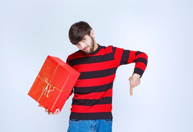 Homme en chemise rayée rouge tenant une boîte-cadeau rouge et appelant la personne juste à côté de lui.
