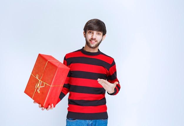 Homme en chemise rayée rouge tenant une boîte-cadeau rouge et en faisant la promotion.