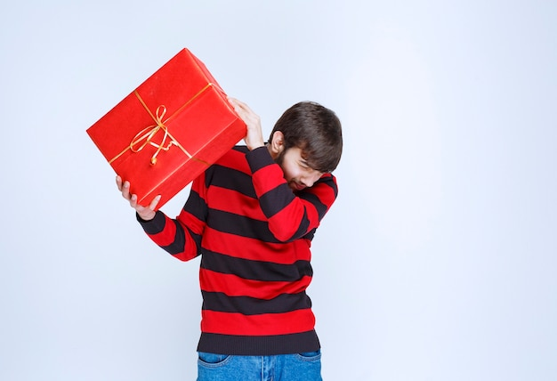 Homme en chemise rayée rouge tenant une boîte cadeau rouge, la livrant et la présentant au client ou à sa petite amie.