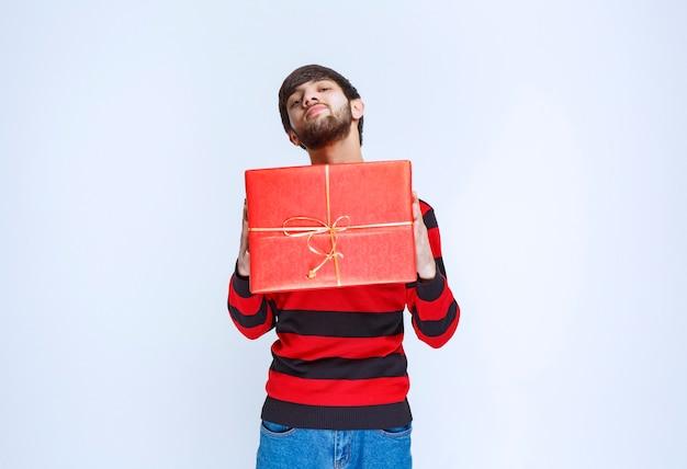 Homme en chemise rayée rouge tenant une boîte-cadeau rouge, la livrant et la présentant