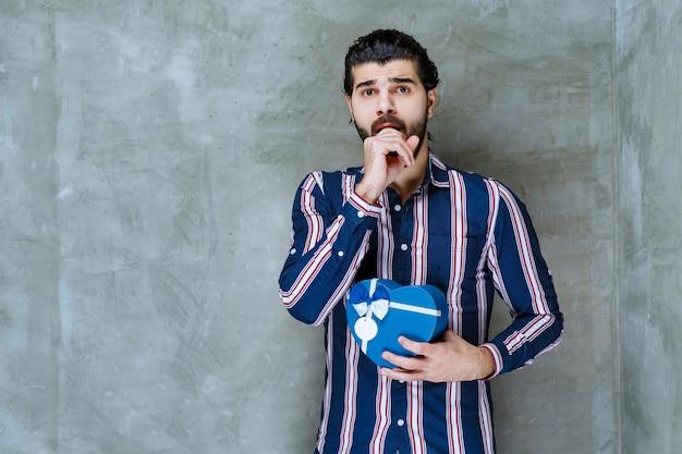 Homme en chemise rayée tenant une boîte-cadeau en forme de coeur bleu et a l'air ravi et effrayé