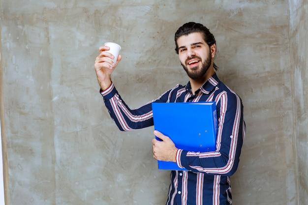 Homme en chemise rayée tenant un dossier bleu et un gobelet jetable blanc