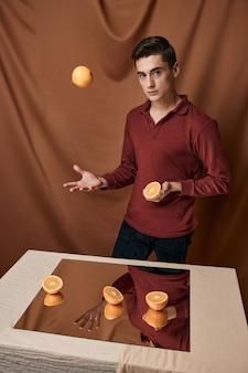 Un homme en chemise rouge avec des oranges près de la table avec un miroir. photo de haute qualité