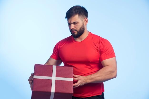 Homme en chemise rouge tenant une grande boîte-cadeau et a l'air sérieux.