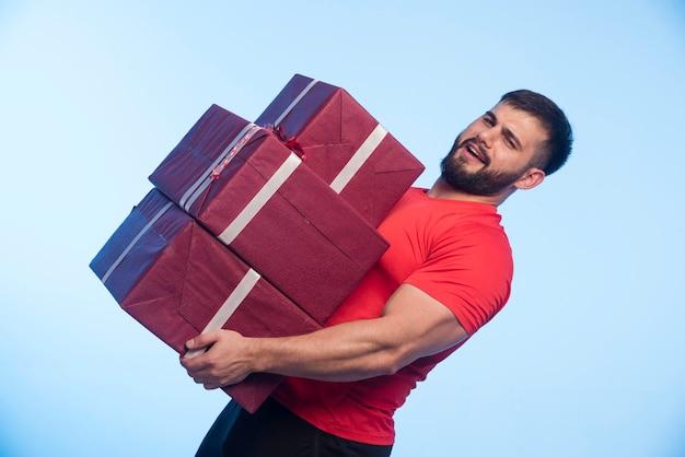 Homme en chemise rouge tenant un gros stock de coffrets cadeaux