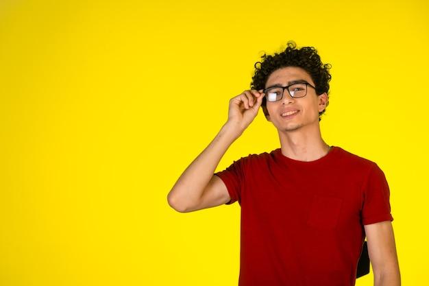 Homme en chemise rouge tenant ses lunettes et souriant.