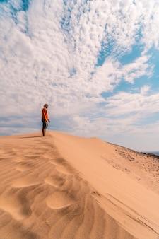 Un homme avec une chemise rouge et un turban sur la tête, marchant dans le désert de la dune