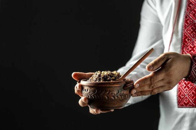 Homme en chemise slave tenant un bol avec de la bouillie de blé kutia traditionnelle