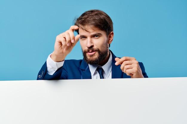 Homme en chemise tenant un panneau publicitaire sur fond bleu.